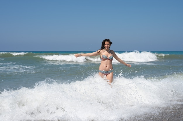 Young woman in a white shirt is bathes in the waves in the sea foam on an exotic tropical island. high quality photo