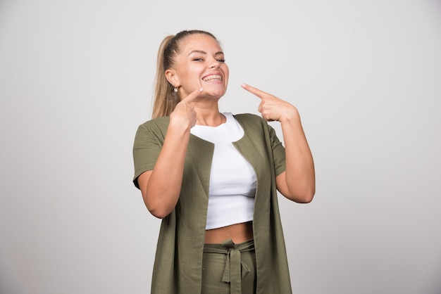 Young woman in white shirt laughing on gray wall.
