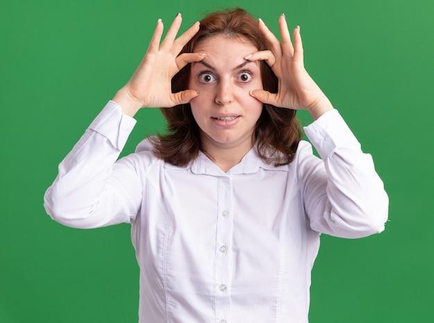 Giovane donna in camicia bianca che osserva ar xamera aprendo gli occhi per vedere meglio in piedi sopra il muro verde
