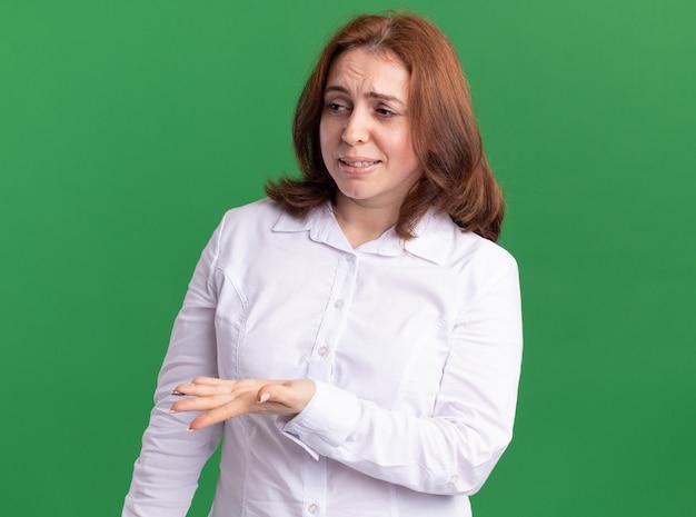 Giovane donna in camicia bianca che osserva da parte alzando la mano in dispiacere e indignazione in piedi oltre il muro verde