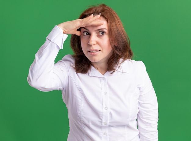 Giovane donna in camicia bianca che guarda lontano con la mano sopra la testa in piedi sopra la parete verde