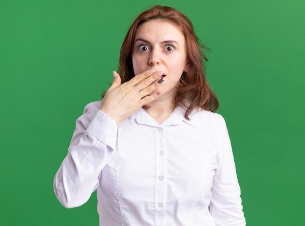 Giovane donna in camicia bianca guardando davanti essendo scioccato che copre la bocca con la mano in piedi sul muro verde