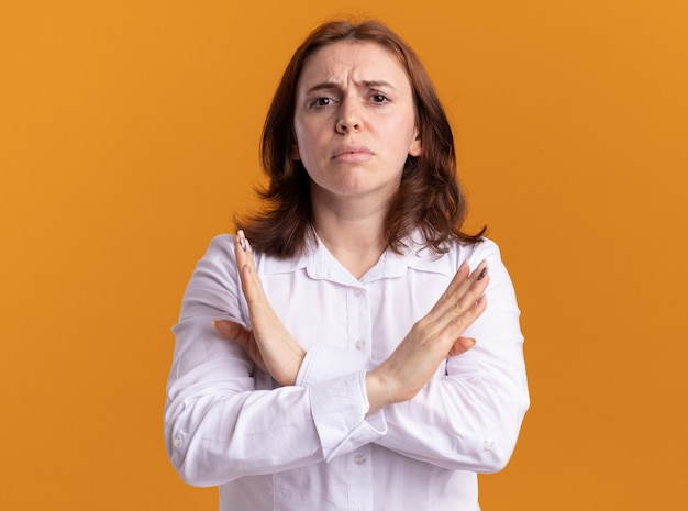 Giovane donna in camicia bianca guardando la parte anteriore con la faccia seria che fa il gesto di arresto che attraversa le mani in piedi sopra la parete arancione