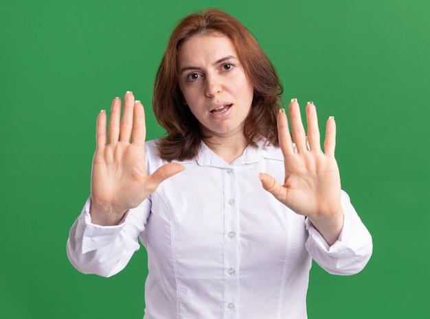Giovane donna in camicia bianca guardando davanti con faccia seria che fa il gesto di arresto con le mani in piedi sopra la parete verde