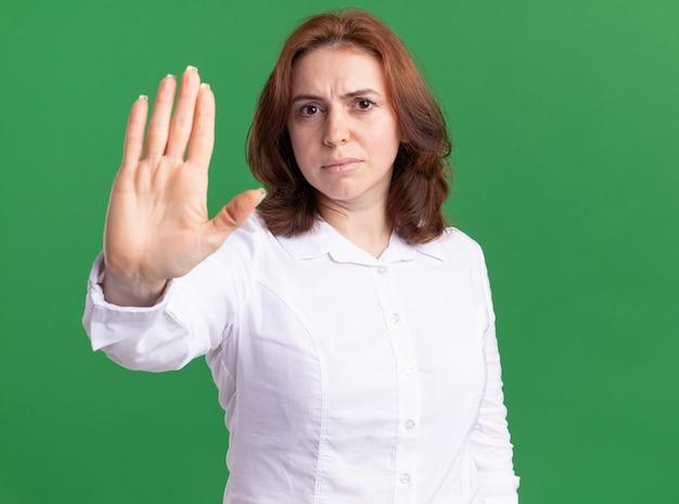 Giovane donna in camicia bianca guardando davanti con faccia seria che mostra il gesto di arresto con la mano aperta in piedi sopra la parete verde