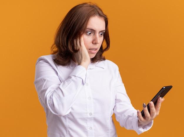 Giovane donna in camicia bianca guardando il suo smartphone rimanendo stupito e sorpreso in piedi sopra la parete arancione