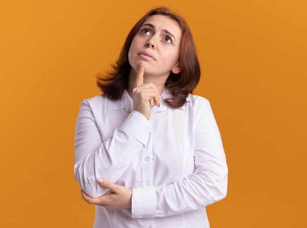 Giovane donna in camicia bianca che osserva in su in piedi perplesso sopra la parete arancione