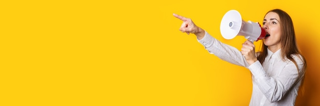 Young woman in a white shirt makes an announcement in a megaphone and points a finger on a yellow background