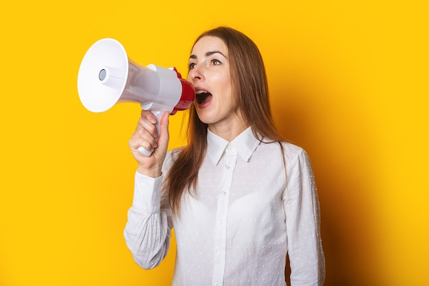 Young woman in a white shirt makes an announcement in a megaphone on a yellow background