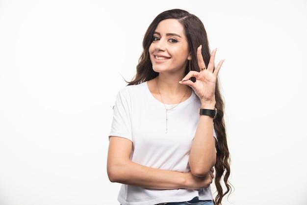 Giovane donna in camicia bianca che fa segno su fondo bianco. foto di alta qualità