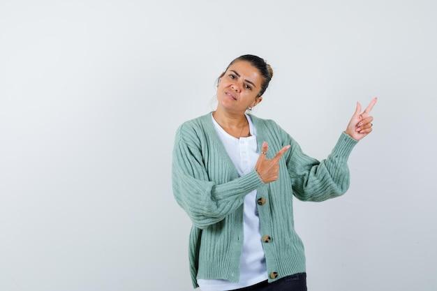 Giovane donna in camicia bianca e cardigan verde menta che punta a destra con l'indice e sembra seria