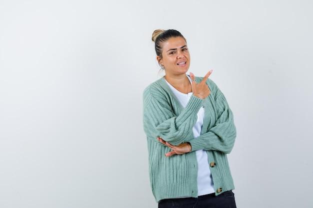 Giovane donna in camicia bianca e cardigan verde menta che punta verso l'alto e sembra felice