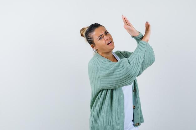 Giovane donna in camicia bianca e cardigan verde menta che mostra restrizione o gesto x e sembra tormentata