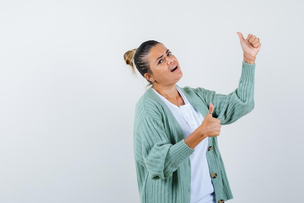 Giovane donna in camicia bianca e cardigan verde menta che mostra i pollici in su con entrambe le mani e sembra felice