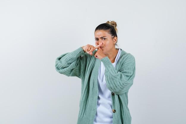 Giovane donna in camicia bianca e cardigan verde menta che mostra il gesto x e sembra tormentata