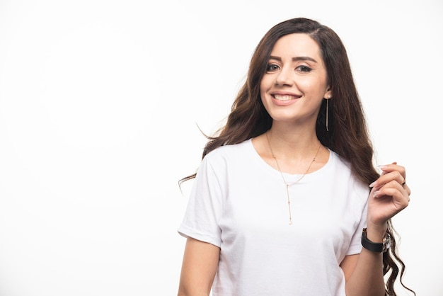 Young woman in white shirt posing on white background. high quality photo