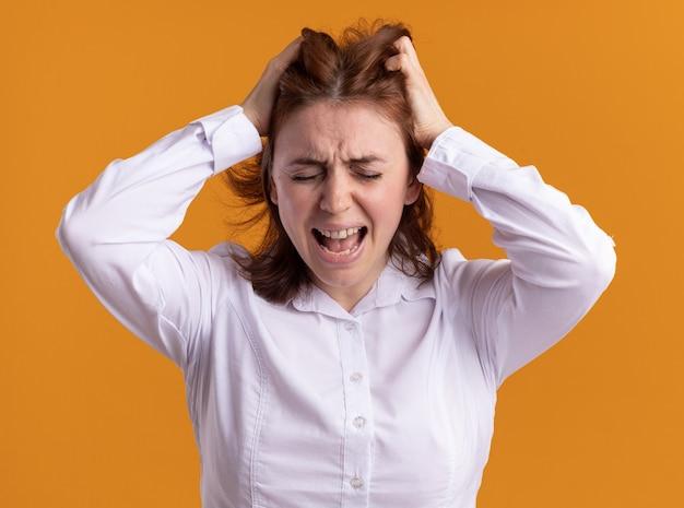 Giovane donna in camicia bianca che grida andando selvaggia tirando i capelli in piedi sopra la parete arancione