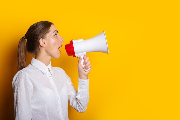 Young woman in a white shirt shouts into a megaphone on a yellow background