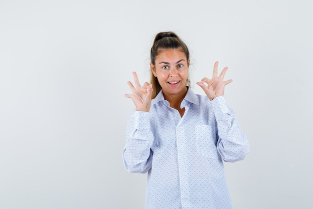 Giovane donna in camicia bianca che mostra segni giusti e che sembra felice