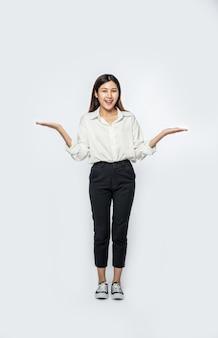 Una giovane donna con una camicia bianca e allargando entrambe le mani