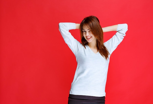 Young woman in white shirt standing on red wall