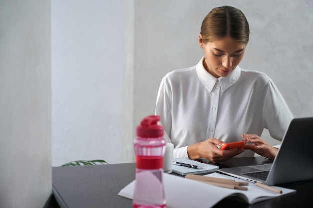 Young woman in white shirt using modern smartphone while sitting at table with laptop and books