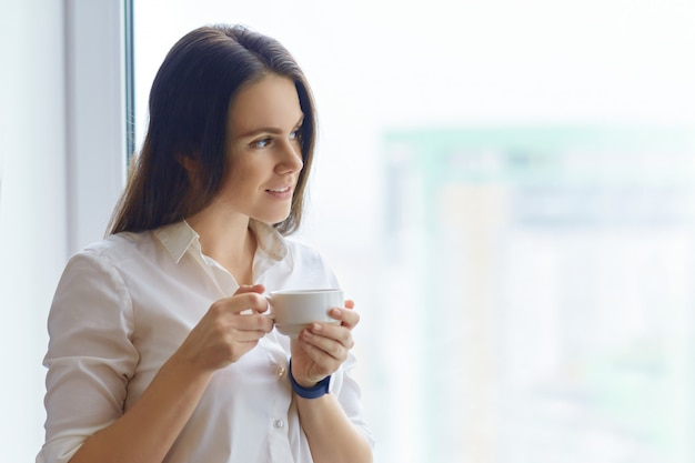 Young woman in white shirt with a cup of coffee near the window