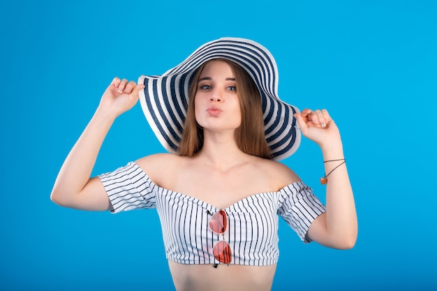 Young woman in white striped swimsuit lingerie and striped hat isolated on blue