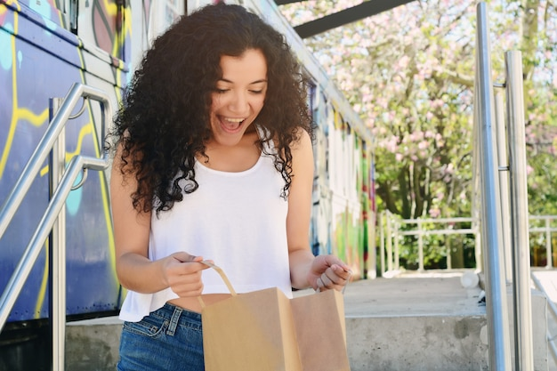 Young woman white surprise face holding shopping bag.