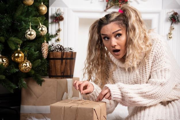 Una giovane donna in maglione bianco che mostra due scatole di regali di natale.
