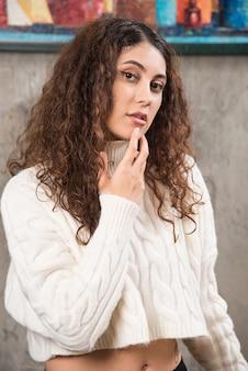 Giovane donna in maglione bianco in piedi e in posa