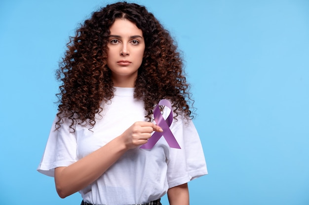 Young woman in white t-shirt holds purple ribbon awareness near heart. symbol of cancer on isolated background
