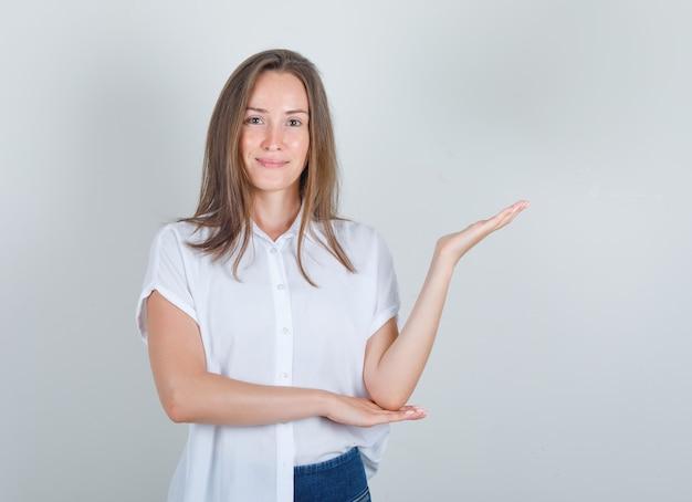 Giovane donna in maglietta bianca, jeans che danno il benvenuto o che mostra qualcosa e che sembra felice
