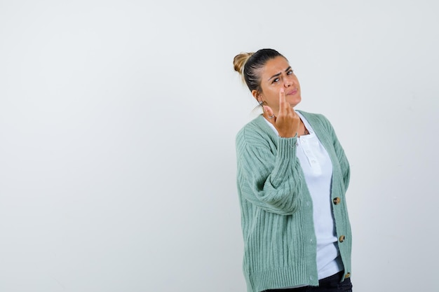 Young woman in white t-shirt and mint green cardigan inviting to come and looking serious