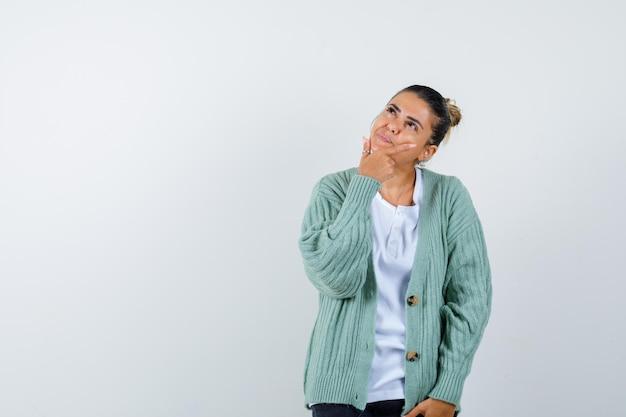 Giovane donna in maglietta bianca e cardigan verde menta in piedi in posa pensante e con aria pensierosa pensi