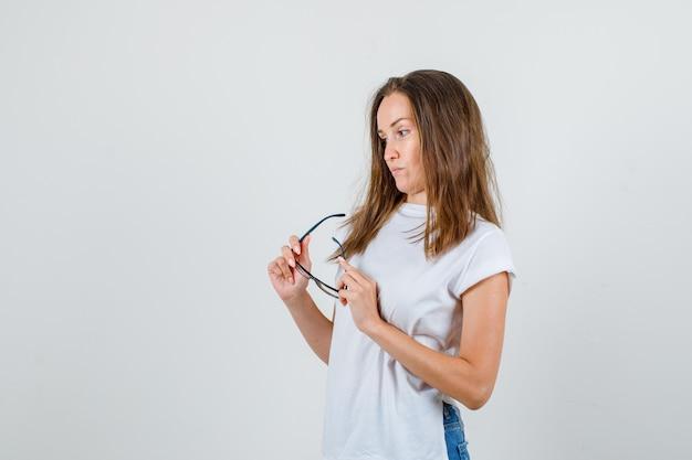 Giovane donna in maglietta bianca, pantaloncini tenendo gli occhiali mentre pensa.