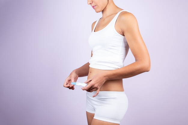 Young woman in white t-shirt and shorts, holding pregnancy test