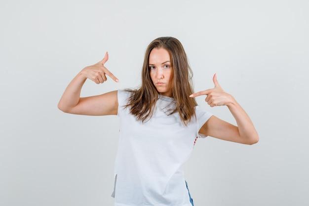 Giovane donna in maglietta bianca, pantaloncini che si mostra con il gesto della pistola e sembra sicura