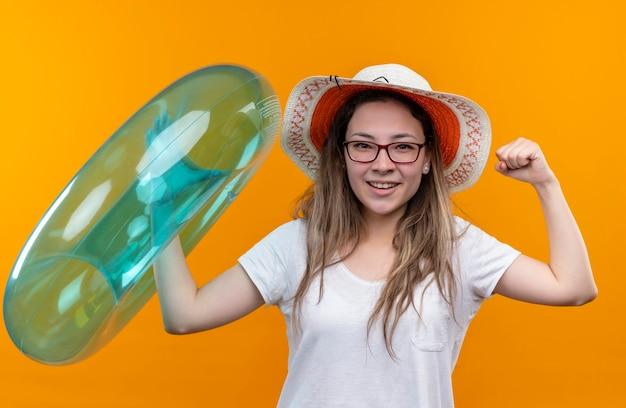Giovane donna in maglietta bianca che indossa il cappello estivo che tiene il pugno di serraggio dell'anello gonfiabile che sembra eccitato e felice che sta sopra la parete arancione