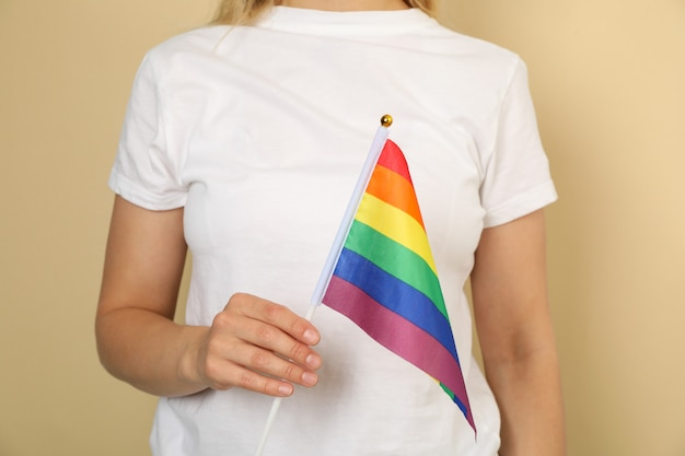Young woman in white t-shirt with lgbt flag against beige