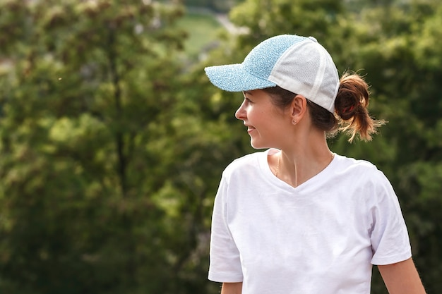 Young woman in a white tshirt and baseball cap on her head looks away on a background of greenery