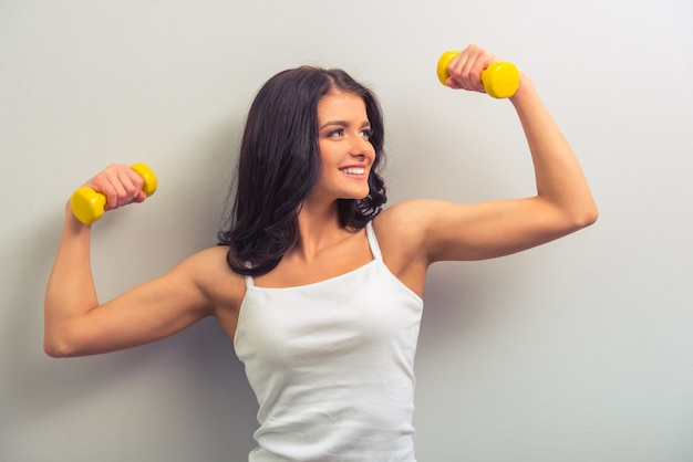 Young woman in white undershirt holding dumbbells.
