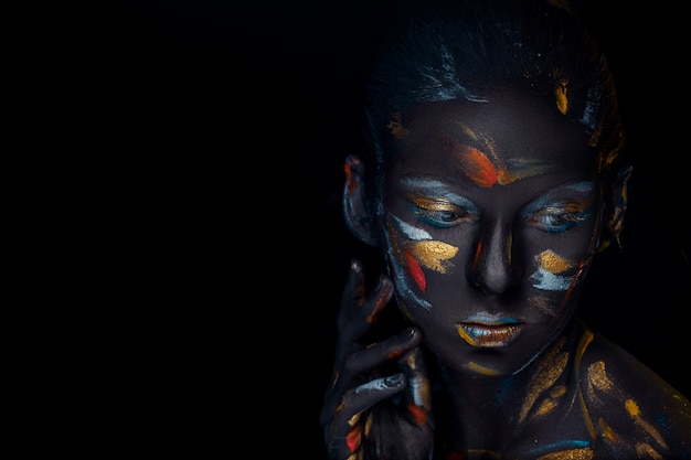Young woman who is posing covered with  black paint