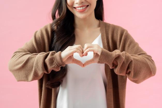 Молодая женщина, которая своими руками делает форму сердца.