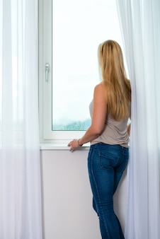 Young woman at window in hotel room