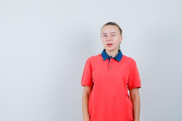 Tシャツで目をまばたきして自信を持って見える若い女性