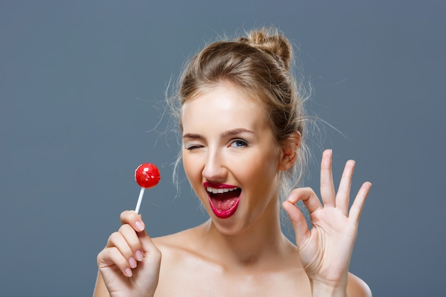 Young woman winking, showing okay, holding lollipop