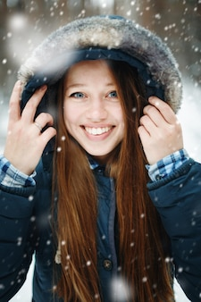 Young woman in winter clothes standing under the snow, smiling, laughing, looking at camera. winter forest landscape and snowfall on the background.