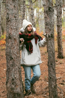 Giovane donna in abiti invernali in piedi accanto agli alberi