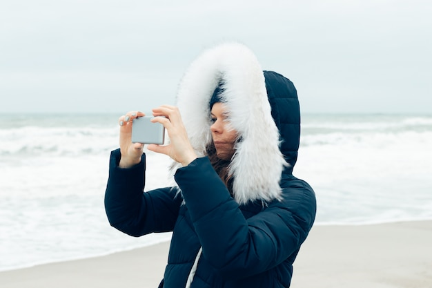 Young woman in a winter jacket with a hood using a mobile phone on the beach